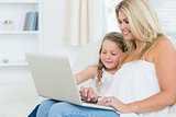 Smiling mother and daughter on the laptop