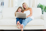 Daughter and mother resting on the sofa with laptop