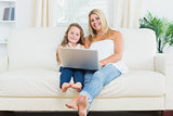 Daughter and mother relaxing on the sofa with notebook