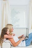 Woman sitting on the couch and using the laptop while her daughter hugging her