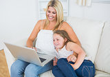 Laughing mother and daughter using notebook