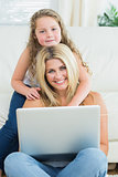 Daughter hugging her mother using laptop