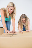 Mother and daughter closing moving boxes