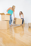 Mother and daughter lifting moving boxes
