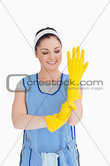 Cleaner woman putting on yellow gloves