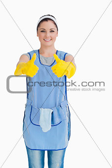 Cleaning woman giving thumbs up with yellow gloves
