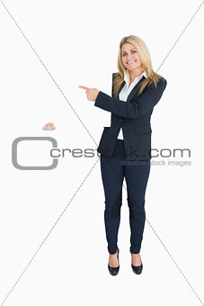Smiling business woman showing a white panel