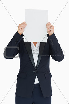 Business woman holding a white panel in front of her face