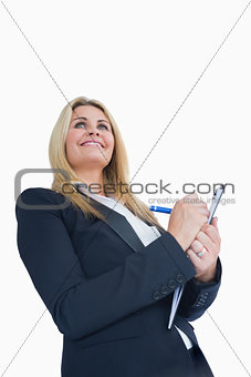 Smiling business woman writing in the clipboard