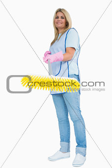 Smiling cleaner woman holding a yellow broom