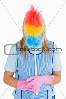 Cleaner holding a feather duster in front her face