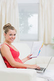 Woman holding cheerfully a notepad and laptop