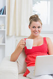 Woman drinking coffee while typing on laptop