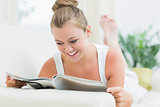 Woman smiling and reading a magazine