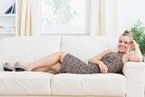 Woman smiling and lying on sofa