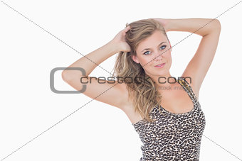 Blonde woman holding her hair and looking glamorous