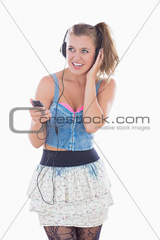 Blonde woman listening to music while smiling