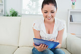 Smiling woman using a tablet pc on the couch