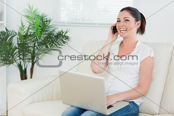 Phoning woman on the couch using a laptop