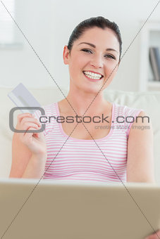 Woman sitting on a couch with a laptop and a credit card