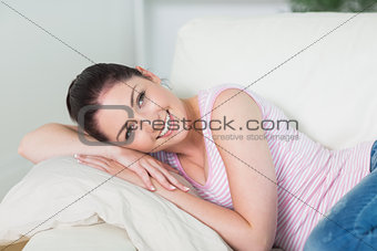 Smiling and relaxing woman lying on a couch
