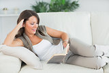 Woman lying on sofa and reading her book