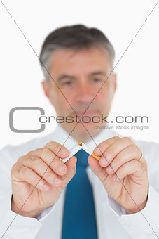 Businessman breaking a cigarette