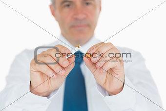 Businessman breaking a cigarette