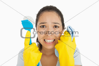 Distressed woman holding cloth and scrubbing brush