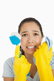 Stressed woman holding scrubbing brush and rag