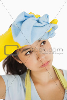 Woman wiping her brow wearing rubber gloves