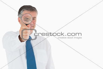 Smiling businessman using magnifying glass