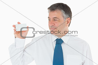 Man holding up and looking at his business card