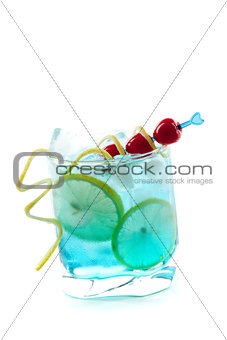 Blue alcohol cocktail with lemon slices and maraschino