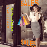 fashion portrait of kitsch shopping girl in front of window shop