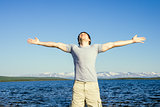 Man traveller standing outdoor  with his hands raised to the blue sky northern landscape mountain and sea on background  Freedom and Happiness emotional concept