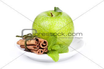 A Ripe Green Apple with mint and cinnamon on plate