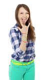 Teenage girl shows tongue and makes hand horns. Mint-colored pan