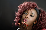 Beautiful black woman on black background blowing a kiss. Afro h