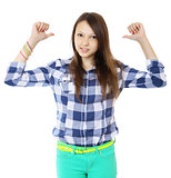 Young teen girl pointing behind with her thumb. Young woman in a