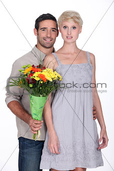 A couple with a bunch of flowers.
