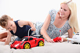 Toddler and mum playing with a remote controlled sports car