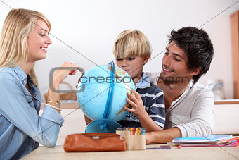 Little boy doing homework with his parents