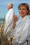 A mature couple down the beach in bathrobe.