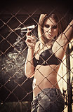 Smoking beautiful young girl stands behind metallic grid