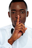 Black man showing silence gesture