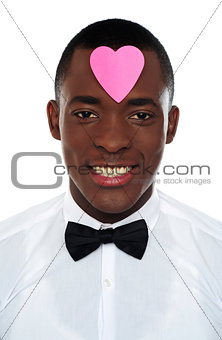 African man with pink paper heart on his forehead