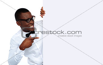 African young man pointing at blank billboard