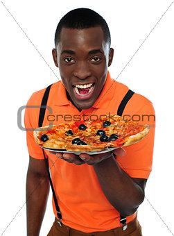 Boy in uniform offering pizza