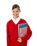Cheerful schoolgirl holding books